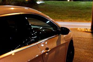 Ein Auto in der Nacht von rechts fotografiert. Man sieht nur die rechte Tür und den Außenspiegel und die Reflektionen auf dem Lack.