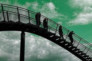 Vier Menschen laufen auf einer Stahlskulptur entlang, die wie eine Achterbahn aussieht. Der Himmel ist grün und hat ein paar Wolken