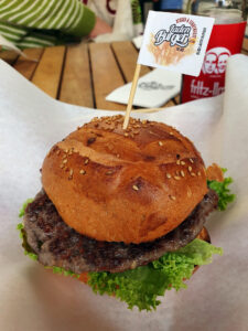 ein leckerer Burger, mit dunklem Brötchen und einer kleinen Fahne obendrauf