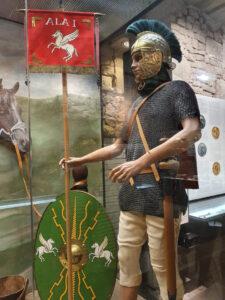 Eine Puppe stellt einen Fahnenträger der Römer dar, mit Kettenhemd und Schild